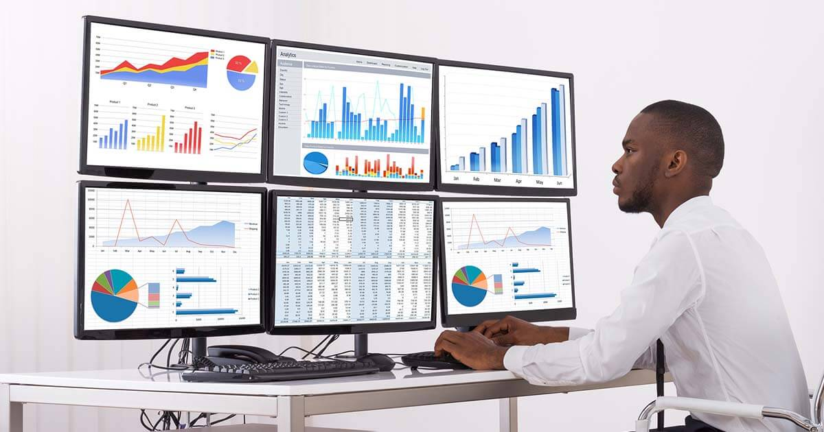 Black person looking at charts on screen - Stock market photo